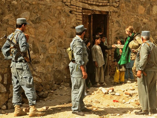 U.S. Air Force Senior Airman Lauren Everett, medic attached to Laghman Provincial Reconstruction Team, greets a group of children in Alisheng district, Laghman province, Sept. 12. The PRT, partnered with the security forces assistant team and the Afghan National Police, patrolled through a village to talk to the locals and teach the ANP proper procedures during patrols.