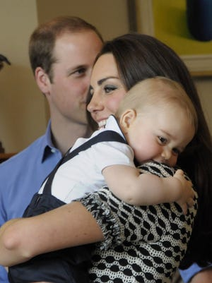 Prince George in Duchess Kate's arms as Prince William looks on during a playdate in Wellington, N.Z. , on April 9, during the Cambridge Down Under tour.