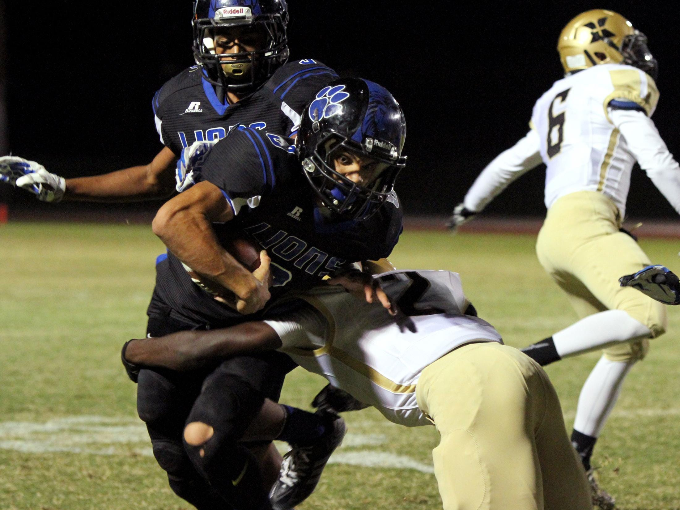 10/02/15 Taya Gray, Special to The Desert Sun Cathedral City's quarterback Cameron Lee tries to break the tackle of Xavier Prep's Fisayo Omilana during the first half of the game in Cathedral City on Friday, October 2, 2015.