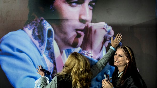 """March 2, 2017 - Shelley Dorazio, left, embraces a picture of Elvis Presley while Jenny Furr laughs inside of the new Elvis Presley's Memphis. Elvis Presley Enterprises opened 200,000 square feet of new exhibits, museums and performance space behind Graceland Plaza, the longtime hub of mansion tours. """"He's mine,"""" Dorazio said. """"I'm not sharing him."""""""