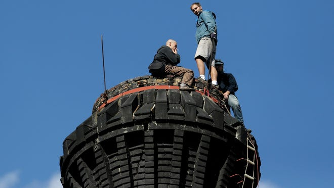 In this picture taken on Saturday, Sept. 27, 2014 in Smrzovka, Czech Republic, enthusiasts rest on top of a 58-meter tall and 100-year-old chimney of a former textile factory. The Czech Union of Chimney Climbers, group of over 1000 members, has climbed and created a database of 9,755 chimneys in the Czech Republic and abroad with details including their exact GPS position, height and condition.