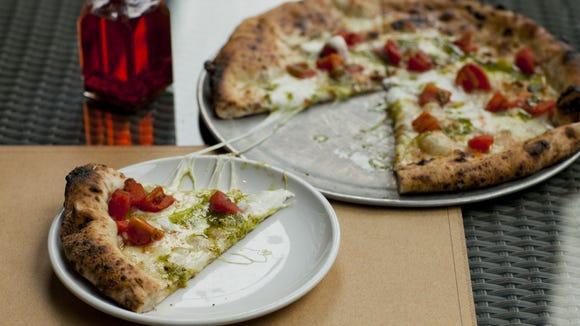 A white tomato pizza is topped with smoked mozzarella,
