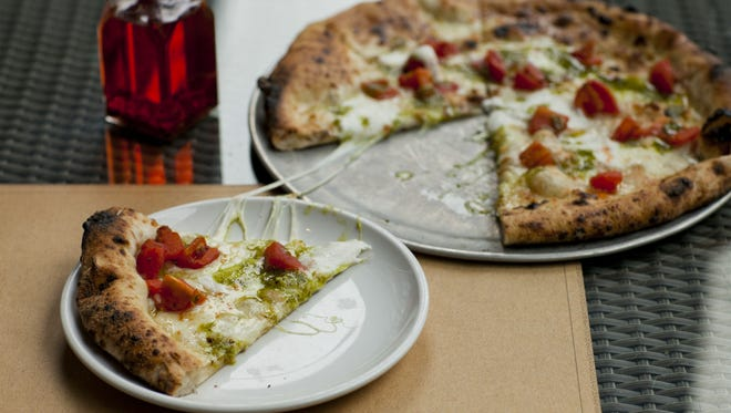 A white tomato pizza is topped with smoked mozzarella, fresh mozzarella and oven-roasted Jersey tomatoes at Treno in Westmont..