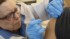 Registered Nurse Susan Jamieson administers a flu shot