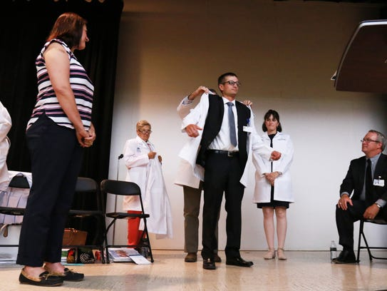 Dr. Ryan Stever receives his new white coat to mark