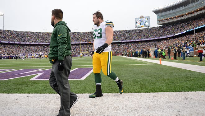 Green Bay Packers center Corey Linsley (63) walks off the field after getting injured during Sunday's game at TCF Bank Stadium in Minneapolis, Minn.