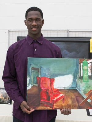 "Chambersburg Area Senior High graduate Ezechiel Cadet holds his his acrylic painting ""Broken Window,"" for which he won the James Patterson Memorial Award for student work during the Franklin County Art Alliance's 45th annual exhibition"