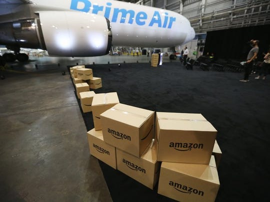 Amazon boxes sitting in an airport hangar in front of a Prime Air cargo plane.