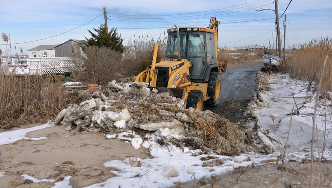 Contractor Bill Erhart of Vineland uses a backhoe to clear debris from the roadway in the Money Island section of Downe Township on Monday.
