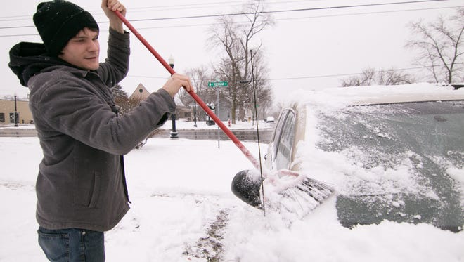 Scott Sharp sweeps off his car Monday, Jan. 29, 2018, on Washington Street in Howell. Sharp says that using a broom keeps the car from getting scratched, and remarked how the weather changed abruptly from the warm temperatures of the past weekend.
