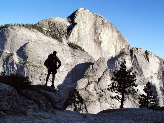 A backpacker views Half Dome, the 8,842-foot symbol of Yosemite National Park, May 30, 2004. A popular trail to the summit of Half Dome approaches from the ridgeline at top left. Cables assist hikers on the final 400-feet, over the steep section in shadow just left of the peak.