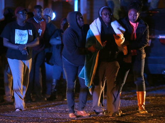A woman is comforted at the scene of a shooting along North 13th Avenue in Humboldt on Tuesday.