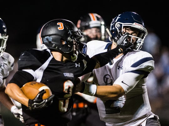 Palmyra's Devon Sosnoski stiff arms Camp Hill's Quinn Buffington as Palmyra defeated Camp Hill 24-21 in the final seconds of their season opener on Friday, August 25, 2017.