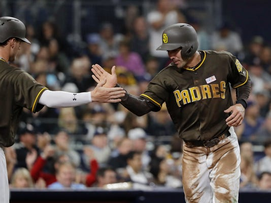 San Diego Padres' Chase d'Arnaud, right, is greeted by Wil Myers after scoring on a single by Allen Cordoba during the third inning of a baseball game against the Colorado Rockies on Friday, June 2, 2017, in San Diego. (AP Photo/Gregory Bull)