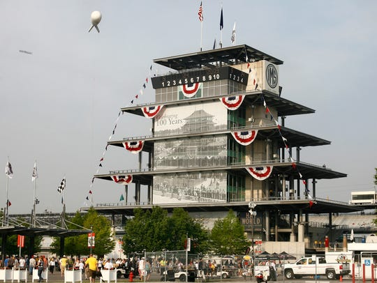Early-arriving race fans walk past the pagoda, decorated