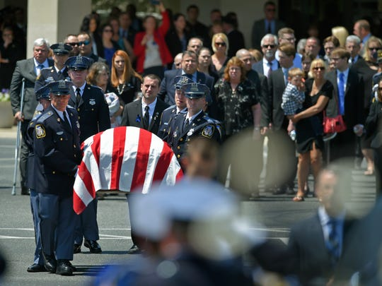 Pallbearers carry the coffin of Officer Amy Caprio during her funeral service Friday, May 25, 2018, at the Mountain Christian Church in Joppa, Md. Caprio was run over by a Jeep while investigating a burglary Monday at a house in Perry Hall.  (Lloyd Fox/The Baltimore Sun via AP)