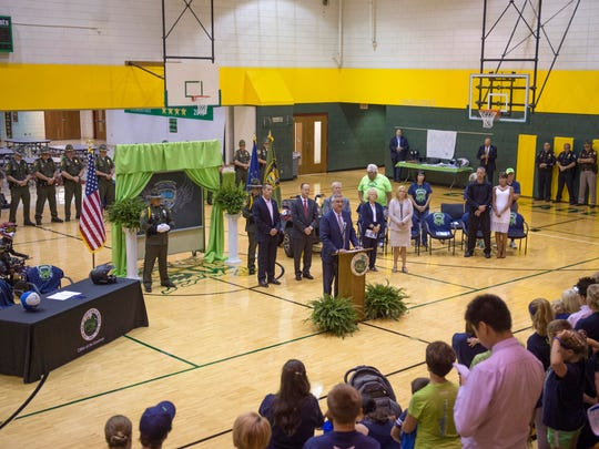 "Gov. Eric Holcomb addresses the crowd at Sharon Elementary School in Newburgh, Ind., before signing the ""Play for Kate"" bill into law Monday morning."