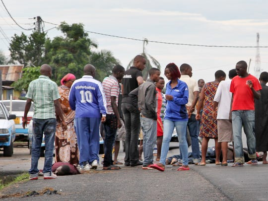 Residents gather to take a look at dead bodies lying in the street in the Nyakabiga neighborhood of Bujumbura, Burundi Saturday, Dec. 12, 2015.