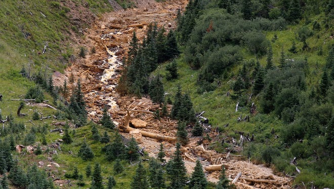 Debris from the Gold King Mine spill cascades down a mountainside Aug. 10 north of Silverton, Colo.