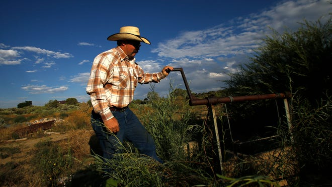 Mike Wright, foreman with the Stacey Ditch, opens the ditch on Aug. 15, 2015, at Sutherland Farms in Aztec after farmers and ranchers were told they could use the Animas River to irrigate their fields after the Gold King Mine spill. The spill in August 2015 released millions of gallons of toxic waste into the Animas River.