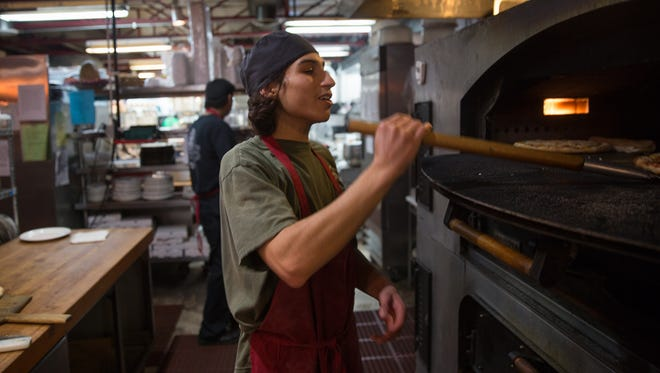 Miguel Zamarron checks to see if a pizza is ready Friday at the Three Rivers Pizzeria in Farmington.