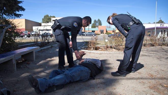Farmington Police District Coordinator Martin Olsen and Officer Brittany Allison assist a down subject Wednesday in Farmington.
