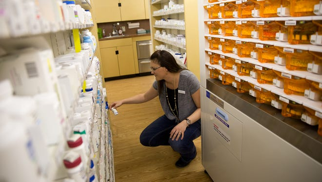 Pharmacist Ashley Seyfarth places a bottle back on the shelf, Monday at Kare Drug in Bloomfield.