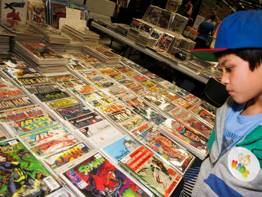 A kid looks at a display of comic books at a Wizard World Comic Con.