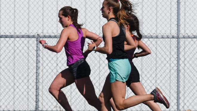Rocori's Brynn Sauer checks her time as she runs during practice Thursday, April 26, in Cold Spring.