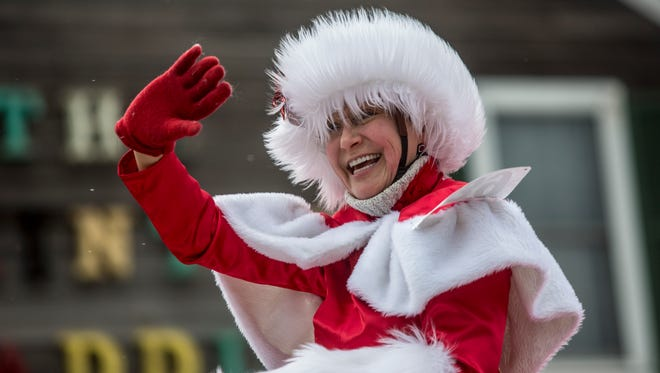 A participant waves from her horse during the 2016 Old Fashioned Christmas Horse Parade in Lexington.