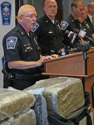 Flanked by Fishers Mayor Scott Fadness (not pictured) and other officers, Fishers Police Chief George Kehl (left) spoke during a news conference at the Fishers Police Department on July 20, 2015.  Fishers police arrested two people and confiscated 100 pounds of marijuana, about $330,000 in cash, three guns and other drugs.