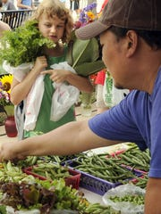 A vendor sells fresh produce at the Stevens Point Farmers