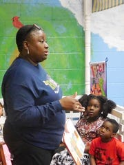 Rhonda Harden discusses a book as Xi'Marra Parks and a classmate look on.
