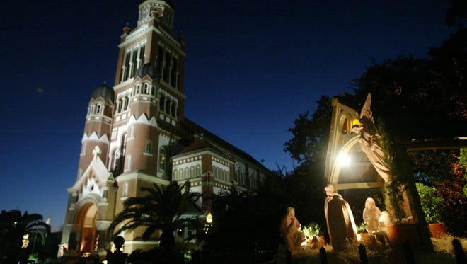 A Nativity scene is illuminated outside before Children's Christmas Mass Thursday evening at St. John the Evangelist Cathedral.