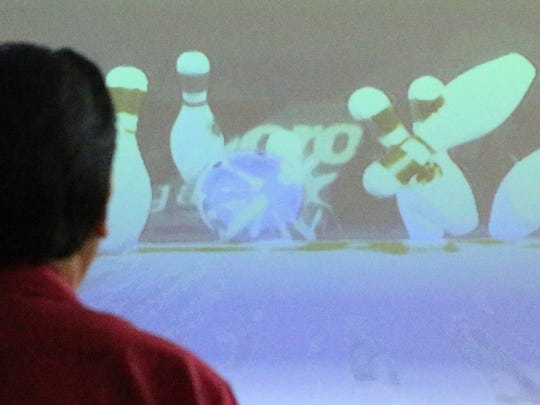 Pat Valtier knocks down the pins during a video game of Kinect Bowling at San Juan Senior Center.