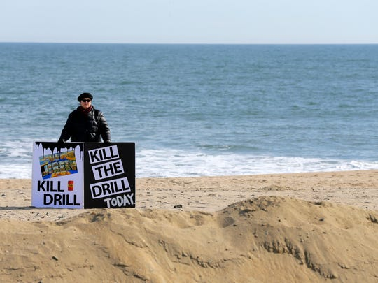 Louise Millmann of Bradley Beach holds signs on the