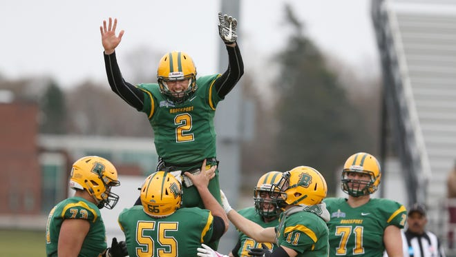 Brockport quarterback Jason Hellwig, 2, is lifted by lineman Mark Sanchez, 55, as they celebrate a touchdown during their NCAA Division III Football Championship first round playoff game