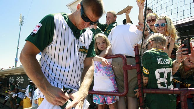 Jordy Nelson signs autographs for fans at the charity softball game in 2014.