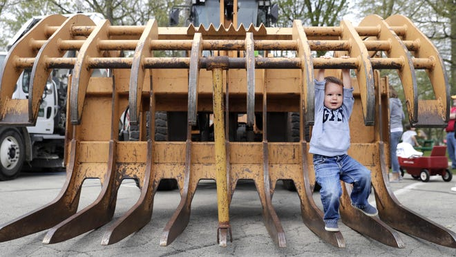 Jack Nudelbacher, 2, of Appleton, hangs from the front claw of a CASE loader May 10 during the Touch-A-Truck event hosted by Neenah Parks and Recreation at Memorial Park. Children were able to view and explore a variety of trucks during the program.