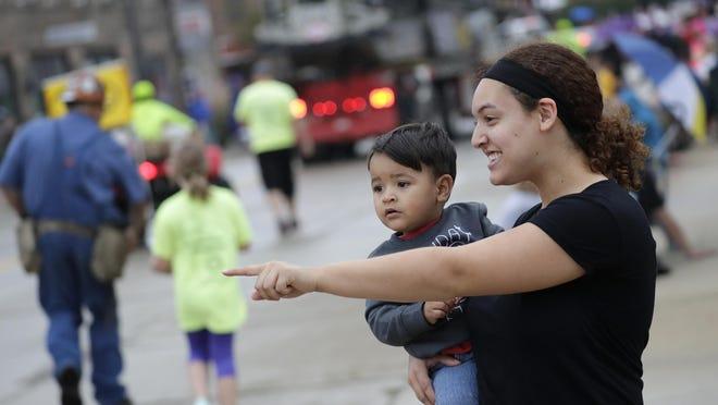Allison Blair of Menasha and her 20-month-old son, Kieran Hazlett, watch the Neenah-Menasha Labor Day Parade on Sept. 4 in downtown Menasha.