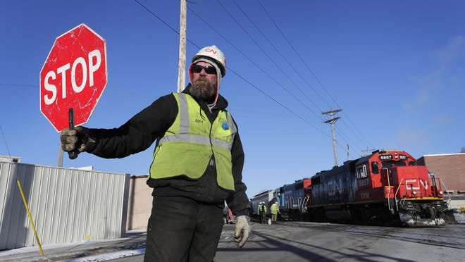 Canadian National Railway employee Todd Vonloh directs traffic Jan. 4 as a train passes by, while fellow crew members replace a broken piece of rail along the North Lake Street railroad crossing in Neenah.