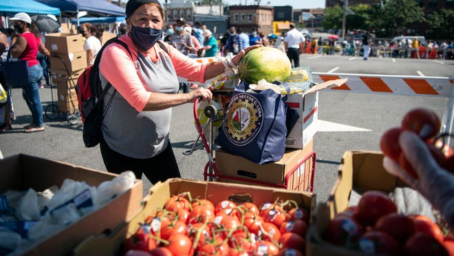 Residents in Passaic, N.J., participate in a food distribution event Wednesday at the Passaic City Hall. New Jersey and Kansas are two of the 45 states in the new SNAP Online Purchasing Pilot program.