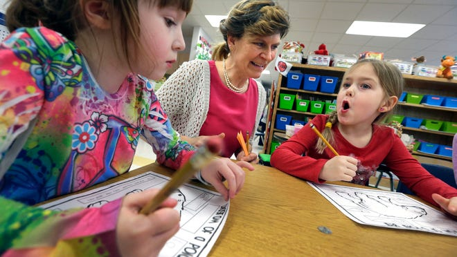 Paraprofessional Lynn Schmalz assists kindergartners Autumn Havel (left) and Aubryn Nord with a writing project at Sunrise Elementary School in Harrison. The Kimberly school district will offer full-day kindergarten starting next school year.