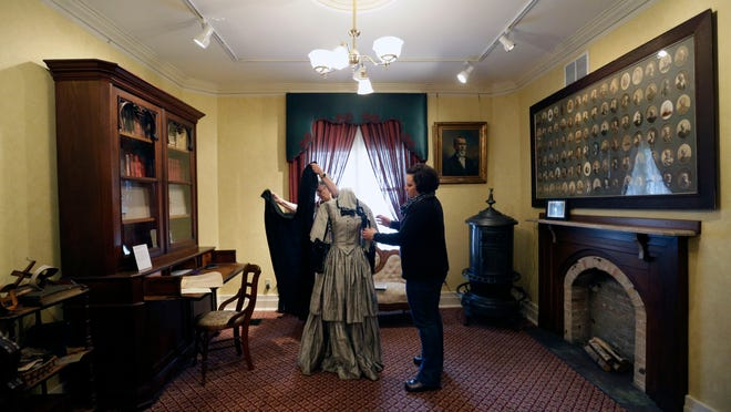 Volunteer JoEllen Wollangk (left) and education and programming coordinator Emily Runnerstrom put together a Civil War era dress typical of someone mourning President Abraham Lincoln's death as part of a Civil War exhibit in the front parlor of the Neenah Historical Society.