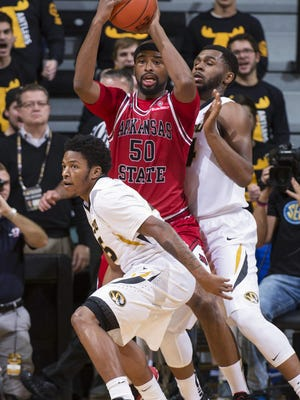 Arkansas State's Anthony Livingston (50) looks to pass as he is surrounded by Missouri's Kevin Puryear, right, and Wes Clark during Tuesday's game in Columbia.