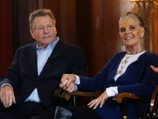 Ryan O'Neal and Ali MacGraw hold hands during talk