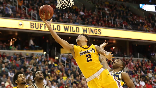 Minnesota Golden Gophers guard Nate Mason (2) shoots the ball past Michigan Wolverines guard Xavier Simpson (3) in the second half during the Big Ten Conference tournament.