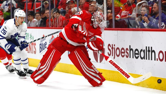 Red Wings goalie Jimmy Howard (35) clears the puck from behind the net in the first period on Friday, Dec. 15, 2017, at Little Caesars Arena.