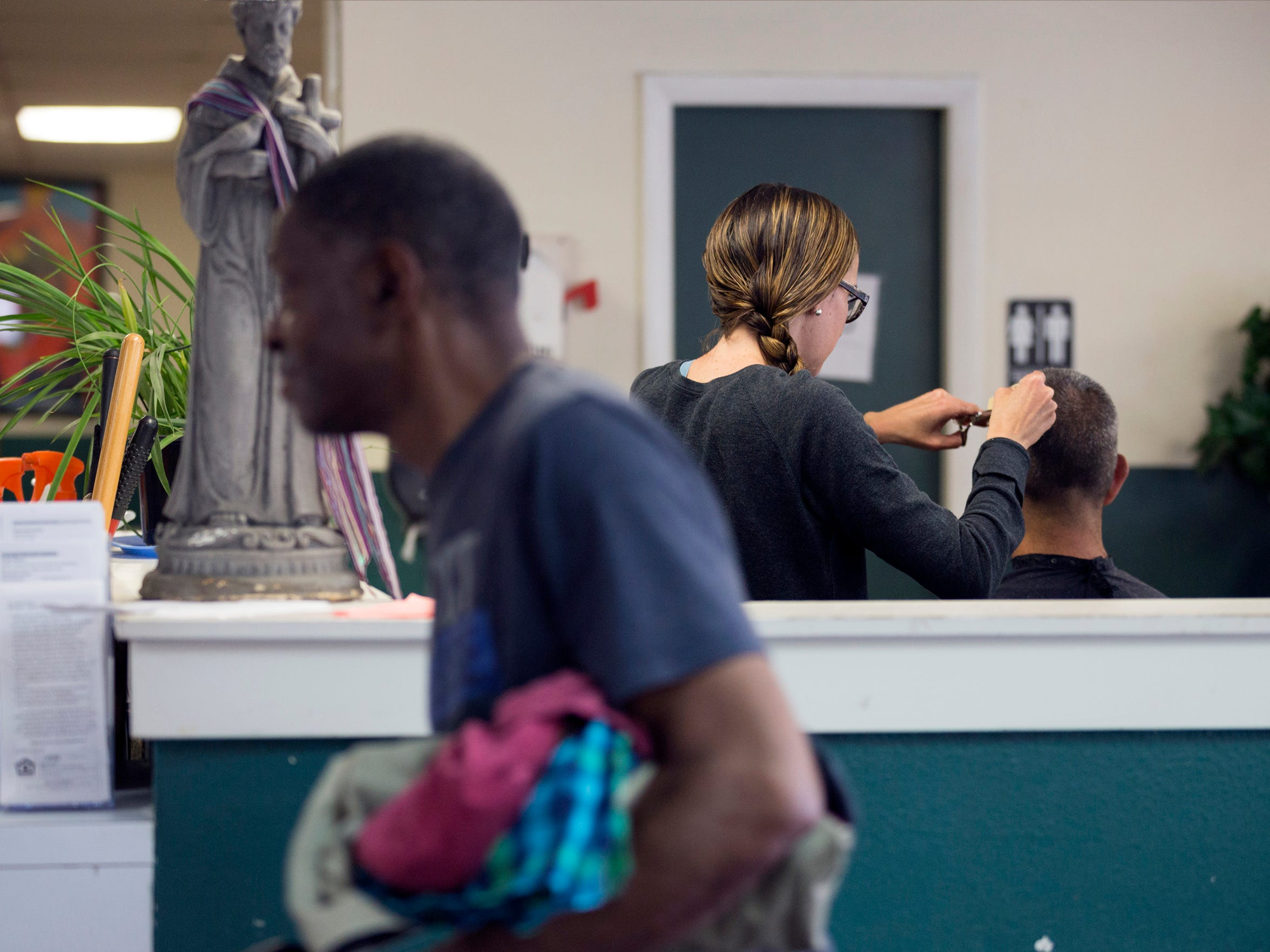 Homeless men gather at the St. Francis Center for meals, service referrals and haircuts in Denver, Colo., Monday, June 18, 2018. The shelter has served increased numbers of homeless people since the legalization