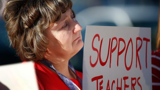 """Nanette Swanson pauses as she listens to another teacher at Tuscano Elementary School talk about the hardships of low pay as teachers, parents and students stage a """"walk-in"""" for higher pay and school funding on  April 11, 2018, in Phoenix. Teachers gathered outside Arizona schools to show solidarity in their demand for higher salaries staging """"walk-ins"""" at approximately 1,000 schools that are part of a statewide campaign for a 20 percent raise and more than $1 billion in new education funding."""